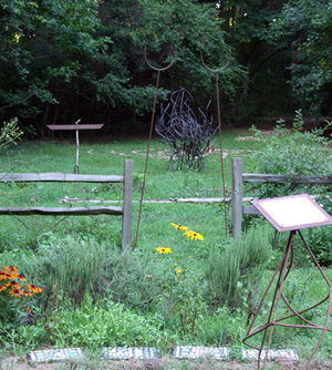 Abstract metal sculpture, in the background of a garden.