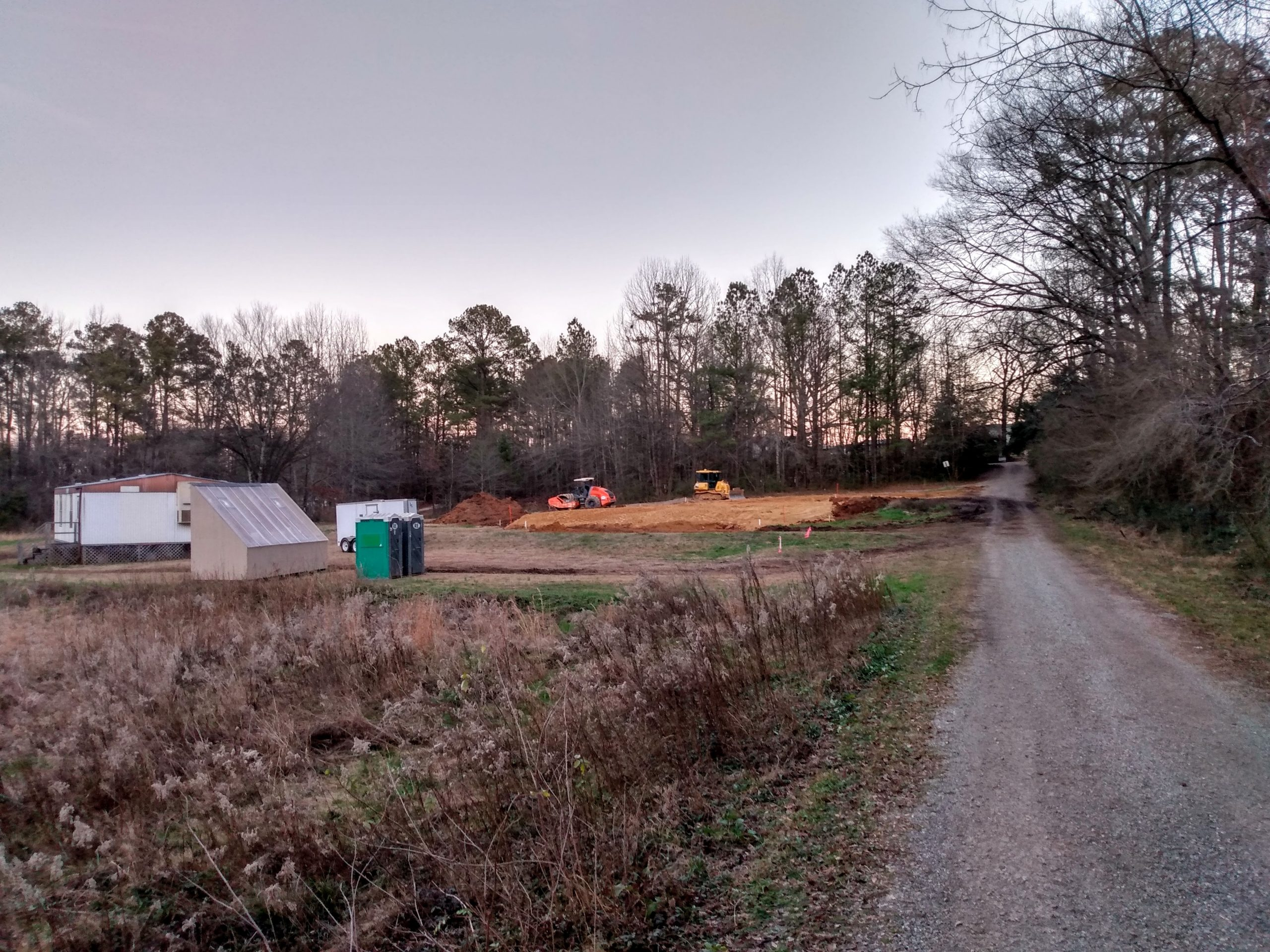 Field in foreground with classroom trailer, solar kiln, and construction site in background.
